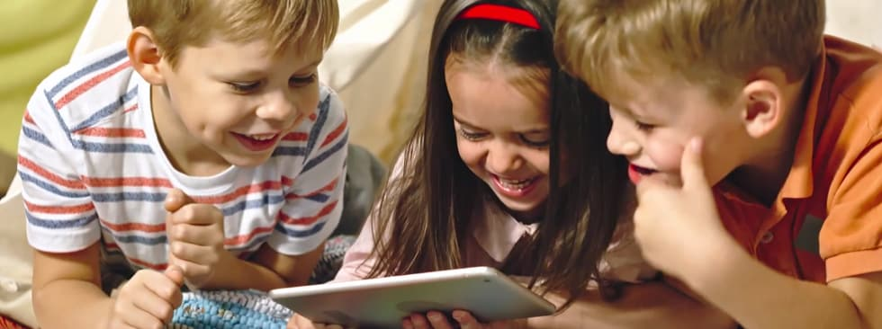 3 kids laughing looking at tablet