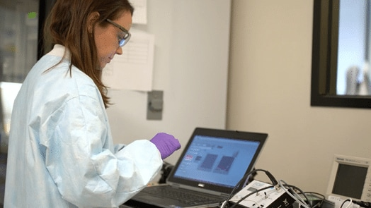 A Draper employee uses a Dell computer while compiling her research