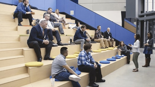 Group of Draper employees sitting in an ampitheater environment listening to a coworker speak