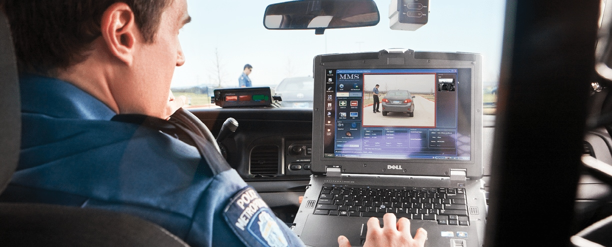 Male police officer in vehicle using Dell notebook computer with dashboard camera showing another male police officer  who is also visible through vehicle s windshield  Dell Photo Shoot in Killeen Texas  Ad Agency - Y R SanFrancisco  Art Director - Juan Contreras