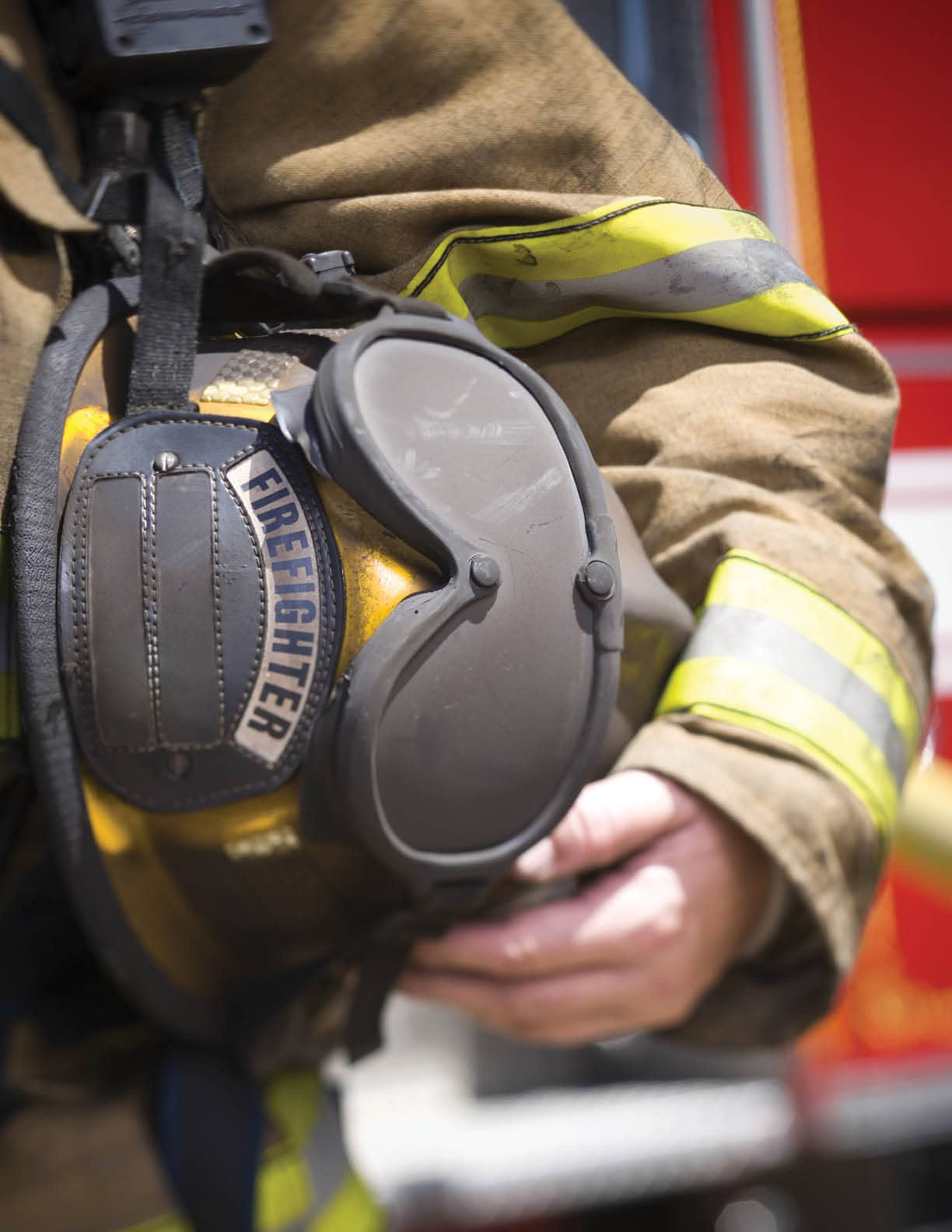 Close-up of a firefighter holding a firefighter s helmet