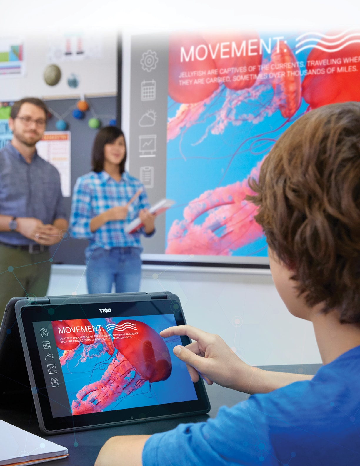 A boy in a classroom controls a Dell S518WL advanced laser projector with a Latitude 3189 2-in-1 notebook (Keystone 11) while two teachers look on  Features screenfill (shutterstock_49279093,   Anna Azimi)